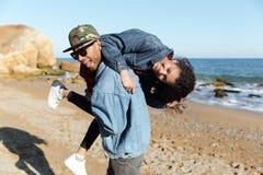 Le afrikanen som älskar par som utomhus går på stranden royaltyfri foto
