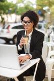 Le afrikansk amerikanflickan i exponeringsglas som sitter på tabellen av kafét och arbete på hennes bärbar dator Härlig dam med fotografering för bildbyråer