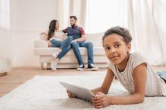 Le afrikansk amerikanflickan som använder den digitala minnestavlan, medan ligga på matta hemma Fotografering för Bildbyråer