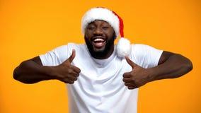 Le afrikansk amerikanjultomten som visar upp tummar, ferier f?r lycklig jul arkivbild