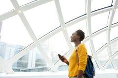 Le afrikansk amerikankvinnan med påsen och mobiltelefonen på stationen fotografering för bildbyråer