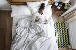Le afrikansk amerikankvinnan på videopn prata för säng Royaltyfria Bilder