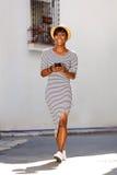 Le afrikansk amerikankvinnan som går med mobiltelefonen Arkivfoto
