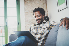 Le afrikansk amerikanmannen i den videopd appellen för headphonedanande via det elektroniska handlagblocket, medan sitta på soffa Royaltyfri Fotografi