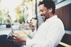 Le afrikansk amerikanmannen i hörlurar som gör den videopd appellen via det elektroniska handlagblocket med bort kaffe för tagand Royaltyfria Bilder