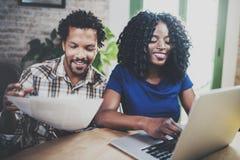 Le afrikansk amerikanpar som tillsammans kontrollerar pappersräkningar på trätabellen Ung svart man och hans flickvän arkivfoton