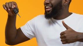 Le afrikansk tangent för grabbinnehavbil och visa upp tummar, automatiskkrediteringsgodkännande stock video