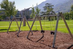 Urban furniture in a public park Trento, Italy. Wooden swing. Residential district Le Albere, designed by the Italian architect Re stock photography