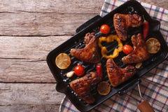 Le ali di pollo del BBQ con le verdure in una pentola grigliano cima orizzontale Fotografia Stock