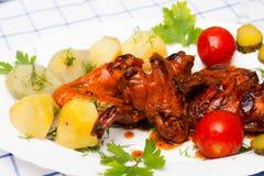 Le ali di pollo hanno grigliato con le patate bollite ed hanno marinato i pomodori Fotografia Stock Libera da Diritti