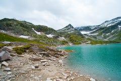 Le alpi abbelliscono - il lago glaciale davanti alle montagne ed al cielo blu Fotografia Stock Libera da Diritti