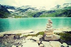Le alpi abbelliscono - il lago glaciale davanti alle montagne ed al cielo blu Immagine Stock