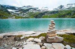 Le alpi abbelliscono - il lago glaciale davanti alle montagne ed al cielo blu Immagini Stock