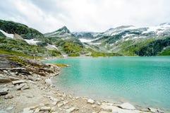 Le alpi abbelliscono - il lago glaciale davanti alle montagne ed al cielo blu Immagini Stock Libere da Diritti