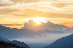 Le alpi ad alba Picchi di montagna maestosi del cielo variopinto, valli della foschia della nebbia Vista espansiva della lampadin Fotografia Stock