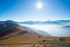 Le alpi in lampadina dalla cima della montagna Vista di autunno con lo sprazzo di sole luminoso ed il chiaro cielo blu Nebbia e f Immagini Stock