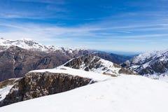 Le alpi nell'inverno, vista sbalorditiva della stazione sciistica della neve di giorno soleggiato dalla cima, picchi di alta mont Immagini Stock