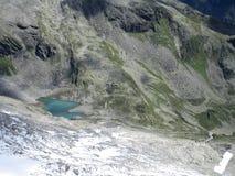 Le alpi - pendio di montagna con il lago blu Fotografie Stock