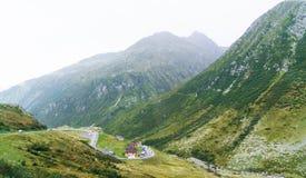 Le alpi svizzere abbelliscono con la strada tortuosa in montagne Fotografia Stock