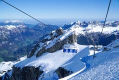 Le alte montagne di vita dello sci nevicano nel fondo del cielo blu dell'inverno Immagini Stock