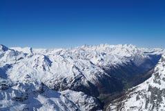 Le alte montagne di vita dello sci nevicano nel fondo del cielo blu dell'inverno Fotografie Stock