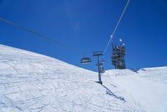 Le alte montagne di vita dello sci nevicano nel fondo del cielo blu dell'inverno Fotografia Stock Libera da Diritti
