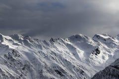 Le alte montagne nevose e la luce solare infuriano il cielo nella sera Immagini Stock Libere da Diritti