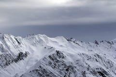 Le alte montagne nevose e la luce solare infuriano il cielo prima della bufera di neve Immagine Stock