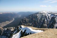 Le alte montagne osservano sopra la città qui sotto Fotografia Stock