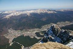 Le alte montagne osservano sopra la città qui sotto Immagini Stock