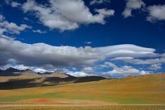 Le alte montagne sono deserto in autunno, le colline sono coperte di giallo e l'erba verde, muschio rosso, cumuli bianchi sta imm Fotografia Stock Libera da Diritti