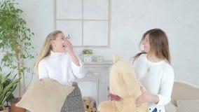 Le amiche delle ragazze stanno combattendo con i cuscini e un orsacchiotto in un tiro di foto stock footage