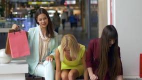 Le amiche di acquisto in vestiti variopinti al centro commerciale esaminano la macchina fotografica ed i sacchi di carta sorriden stock footage