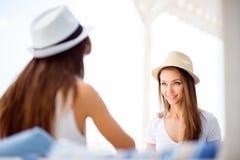 Le amiche felici stanno sedendo di estate fuori del lig dell'aria aperta Immagini Stock Libere da Diritti