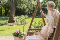 Le anhörigvårdaren och den lyckliga äldre kvinnan på terrassen under solig dag arkivfoton