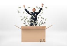 Le anseende för affärsman i öppna stora pappbrevlåda- och dollarräkningar faller runt om honom, isolerat på Royaltyfri Bild