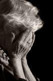 Le anziane tristi con le sue mani al suo fronte è costernazione Immagini Stock Libere da Diritti