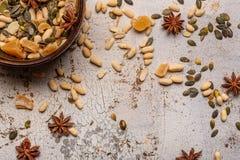 Le arachidi Anise Stars Candied Ginger ed i semi di zucca in un piatto di Brown su bianco e su oro hanno fenduto il fondo struttu fotografia stock libera da diritti