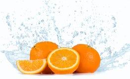 Le arance con acqua spruzza fotografia stock libera da diritti