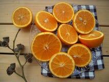 Le arance incidono le metà, per faccia il succo ed il ramoscello asciutto, natura morta immagini stock libere da diritti