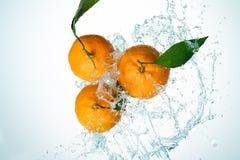 Le arance innaffiano la spruzzata immagini stock