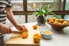 Le arance sono schiacciate a mano per produrre un succo d'arancia puro e sano Fotografia Stock