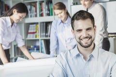 Le arkitekten som ser kameran, medan kollegor planerar runt om en tabell och att se en ritning Arkivbilder