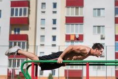 Le armi adatte di allenamento dell'uomo fuori sulle barre orizzontali delle immersioni che preparano fare del bicipite e del tric Immagine Stock
