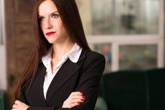 Le armi della femmina della donna di affari hanno attraversato il posto di lavoro serio dell'ufficio fotografia stock libera da diritti