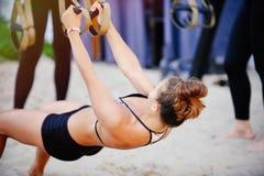 Le armi di allenamento delle donne con le cinghie di forma fisica del trx in natura fanno uno spingere verso l'alto il tricipite  Fotografie Stock