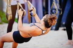 Le armi di allenamento delle donne con le cinghie di forma fisica del trx in natura fanno uno spingere verso l'alto il tricipite  Fotografie Stock Libere da Diritti