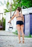 Le armi di allenamento delle donne con le cinghie di forma fisica del trx in natura fanno uno spingere verso l'alto il tricipite  Immagini Stock Libere da Diritti