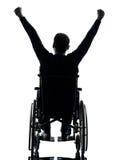 Le armi handicappate dell'uomo di retrovisione si sono alzate nella siluetta della sedia a rotelle Immagine Stock