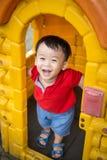 Le asiatet behandla som ett barn pojkehuvudet ut ur plast- dörr Arkivbilder